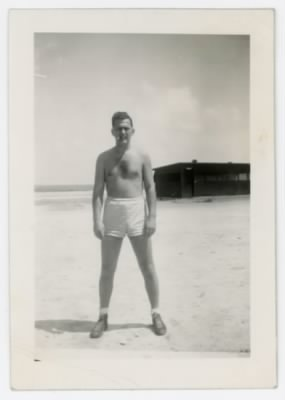 William E. Prettyman in shorts on a beach on the Kwajalein Atoll